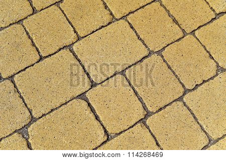 closeup of a yellow stone wall or a stone pavement background in diagonal