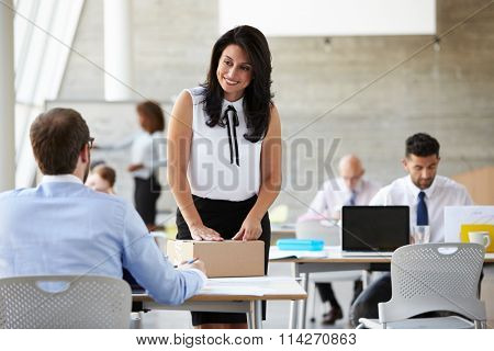 Businesswoman In Office Addressing Package For Shipping