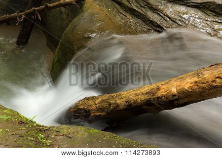 Tranquil stream cascading over stones and branches at Hocking Hills State Park Ohio.