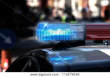 Police Patrol Car With Flashing Lights And Siren On During The Night Raid