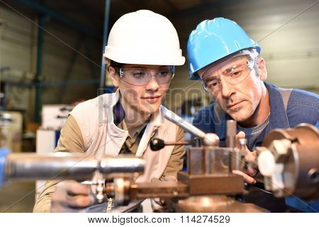 Metal worker teaching trainee on machine use