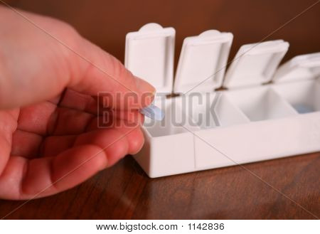 Placing A Pill In A Weekly Pill Box