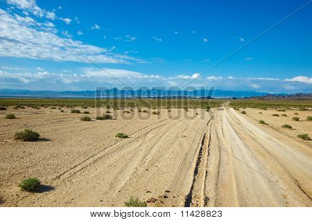 Dry road through steppe in far mountains in bright day poster