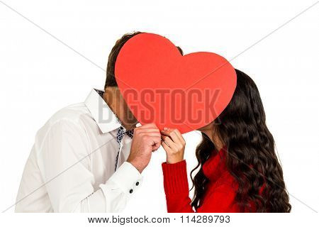 Couple covering faces with paper heart on white background