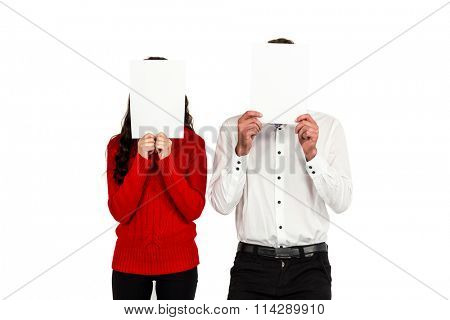 Couple covering their faces with documents on white background