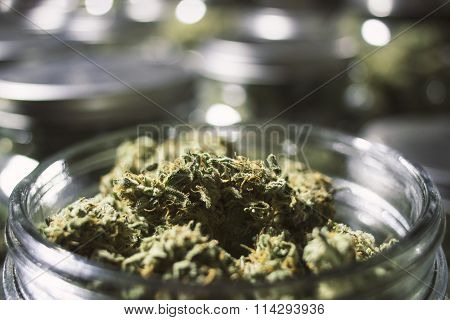 Close Up Marijuana Buds in Glass Jar with Blurry Background