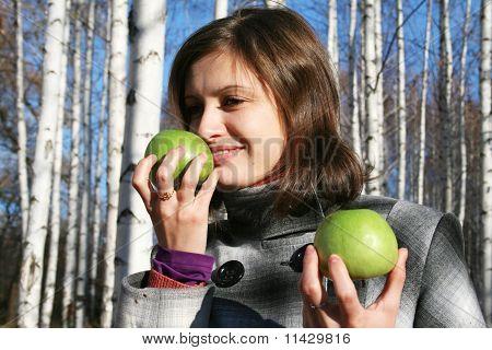 Молодая девушка с двумя зеленые яблоки в березовых дров