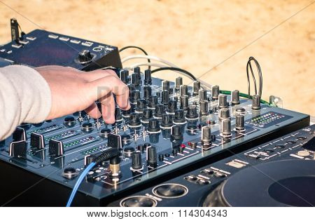 Hand Of A Deejay Playing Music On Professional Mixing Controller At The Beach