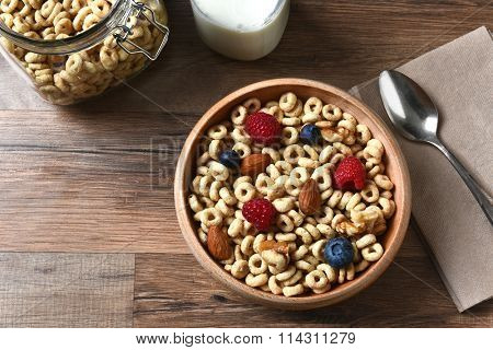 High angle view of a bowl of breakfast cereal with blueberries, raspberries and nuts. A bottle of milk and spoon are also on the rustic wood table, with copy space.
