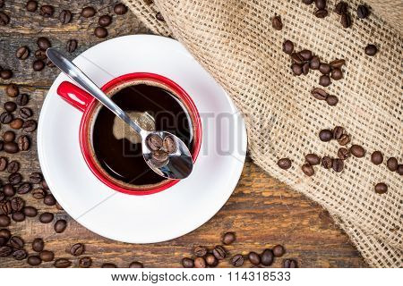 Coffee Beans On Spoon On Top Of Coffee Cup