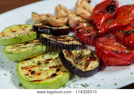 Grilled vegetables on a white plate. Zucchini, tomatoes, peppers grilled.