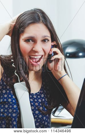 Hispanic brunette sitting by office desk talking on telephone with occupied and worried facial expre
