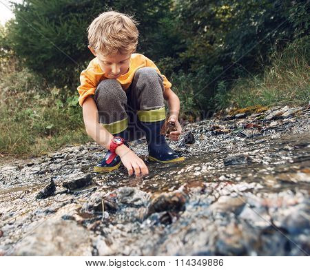 Boy In Gum Boots Playing The Into Te Forest Stream