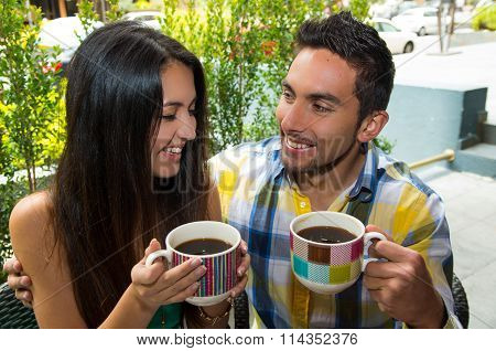 Hispanic cute couple enjoying coffee during a cozy date outdoors and green vegetation background