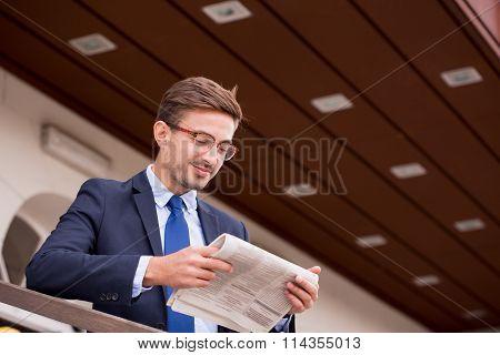 Businessmna Reading Newspaper On Station