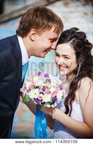 The bride and groom are rolled with laughter, giggle, laugh merrily. Groom in a turquoise tie, he le