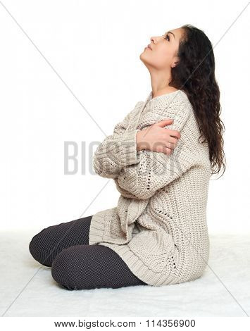 woman portrait in homelike dress sit on fur floor, white background