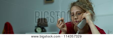 Depressed Woman Listening To Voicemail