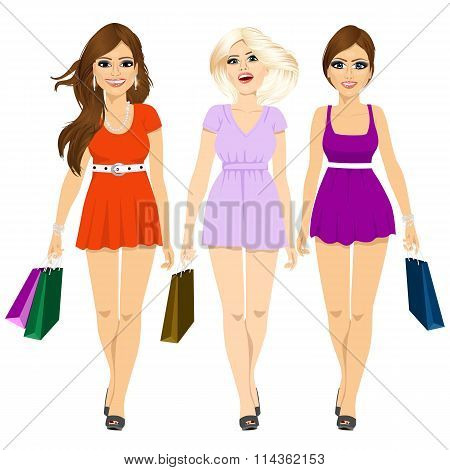 three young attractive smiling girls in summer mini dresses walking and holding shopping bags