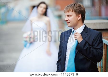 The groom dark blue suit straightens turquoise tie with a sour face, in background tired and frustra