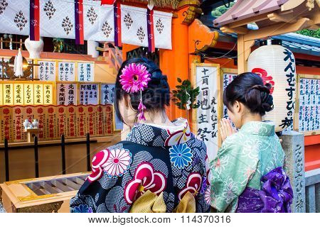 Kyoto, Japan - October 14, 2015 : Two Japanese Girls Dressed With Kimono Praying In A Shrine