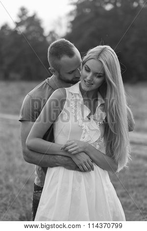 Black and white photo biker couple on a motorcycle in the field. Transferred passionate love photography. Beautiful and motorcycle accessories. Photo for motorcycle poster