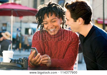 Portrait of happy young couple sitting ouside the cafeteria with smartphone. Close up of couple smiling and looking at mobile phone sitting on table in a coffee bar. Smiling couple having coffee.
