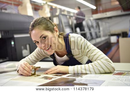 Woman working in print shop, checking document