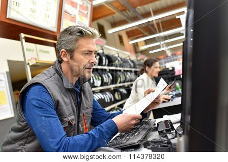 Mechanic in car shop editing invoice on computer