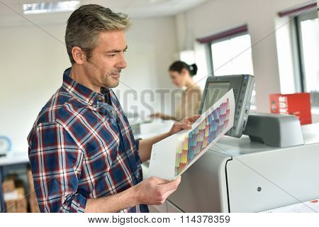 Man working in printing house, programming printer machine
