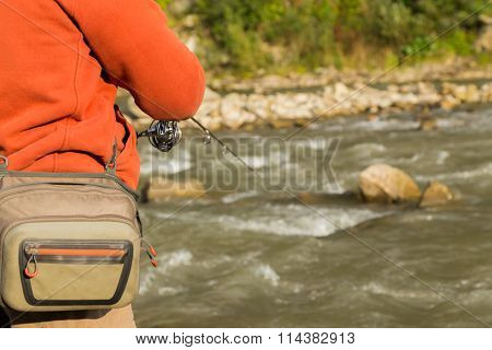 Fishing athlete on a mountain river. Fishing on the course.