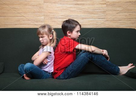 Brother and sister  wearing casual clothes  sitting on a green sofa back to back sad and frown
