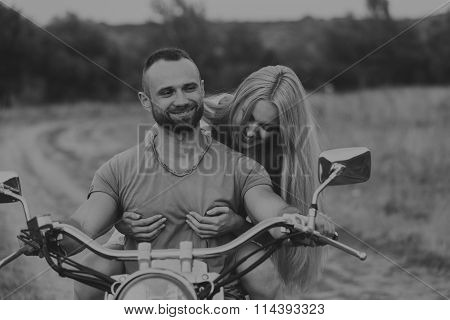 Black and white photo biker couple on a motorcycle in the field.