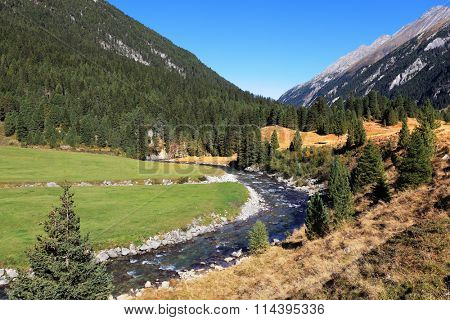 Headwaters of waterfalls - the narrow fast  river among green mountain meadows. National Park Krimml Waterfalls in Austria