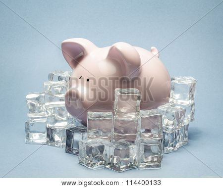 Piggy bank surrounded by ice cubes on blue