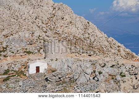 A small chapel and old stone windmill in the rocky hills above Chorio on the Greek island of Halki.