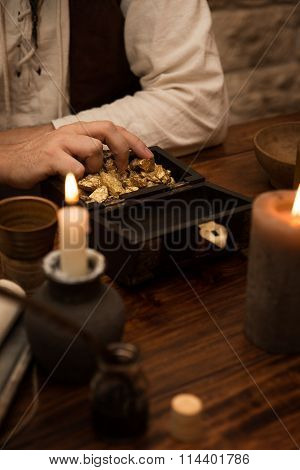 Pirate With A Treasure Of Gold, Medieval Table With Candles, Quill And A Mug