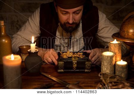 Pirate With A Treasure Of Gold, A Lot Of Candles And Old Accessoires