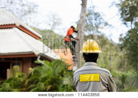 Electrician lineman working on electric post power pole