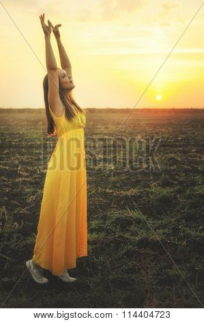 Happy young woman dancing and praising nature with raised hands, enjoying sunset autumn field, gazing into infinity.