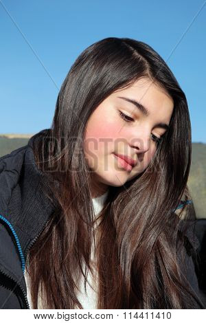 Young teenage european girl with long dark hair in a thoughtful mood against blue sky background.
