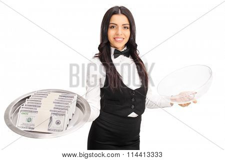 Cheerful female waitress holding a metal tray with a few stacks of money on it isolated on white background