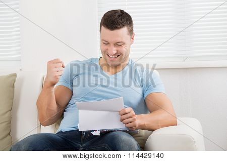 Man Clenching Fist While Reading Letter On Sofa