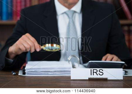 Auditor Examining Documents With Magnifying Glass At Table