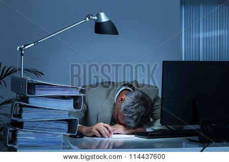 Businessman Leaning Head On Desk By Binders While Working Late