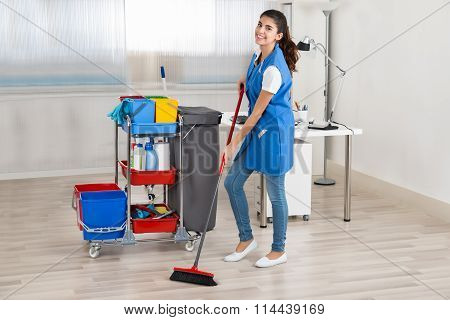 Happy Female Janitor Cleaning Floor With Broom In Office