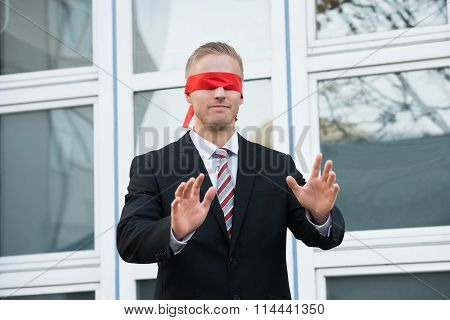 Blindfolded Businessman Standing Against Window