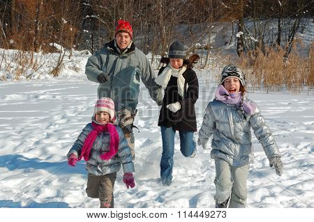 Happy family winter fun outdoors, smiling active parents with kids playing with snow on winter