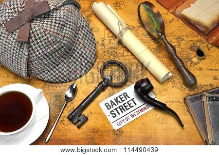 Private Investigation Concept. Sherlock Holmes Deerstalker Cap Full Teacup Sign BAKER STREET Roll Of Paper Vintage Magnifier Retro Key Shabby Book and Notes On The Old Map Background. Top View.