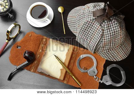 Private Detective Tools On The Black Wood Table Background. Deerstalker Hat Opened Notebook With Blank Brown Page Pipe Magnifying Glass Cuffs Fountain Pen